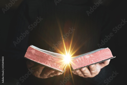 Fototapeta  Light coming from book in woman's hands in gesture of giving, offering