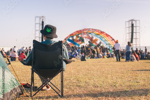 Back view of Man sitting chair on the grass, enjoying an outdoors music, culture, community event, festival,Funny group of young girls and boys at music festival, Happy teen at summer festival Fototapeta