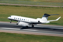 White Modern Private Jet Landing At Airport