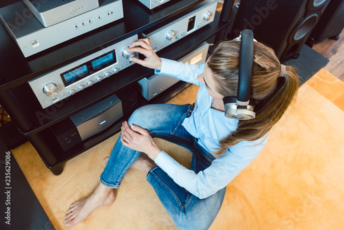 Woman with headphones listening to music via the Hi-Fi stereo in her home Canvas Print