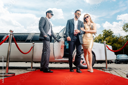 Fotografía  Couple arriving with limousine walking red carpet, a driver is opening the car d