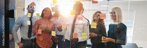 Diverse coworkers brainstorming together with sticky notes in an