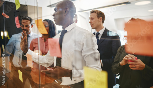 Diverse office colleagues brainstorming together with sticky not