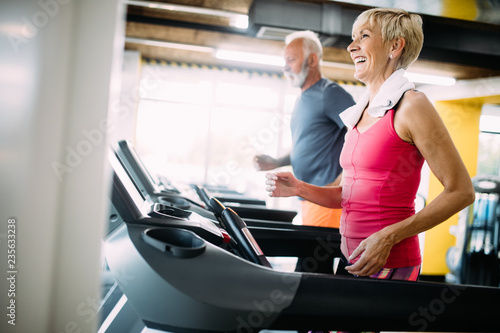 Fotografija  Senior people running in machine treadmill at fitness gym club
