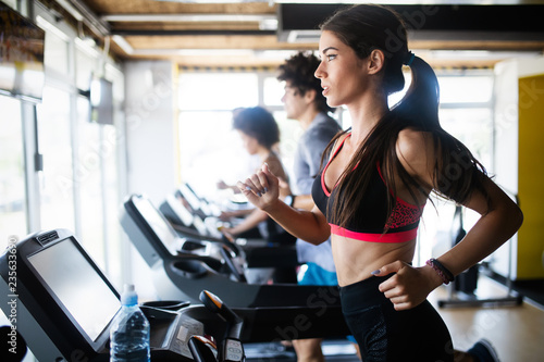 Young people running on a treadmill in health club.