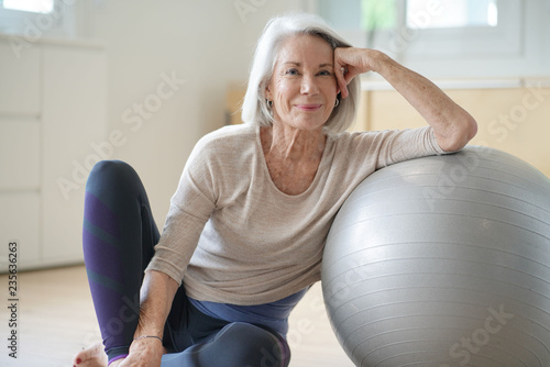 Obraz  Smiling elderly woman resting on a swiss ball at home - fototapety do salonu