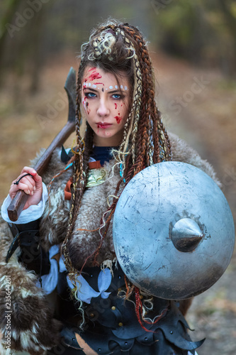 Outdoor portrait of Viking woman warrior in woods with specific makeup, braided hair and face covered in blood holding ax and shield, looking dangerous Wallpaper Mural