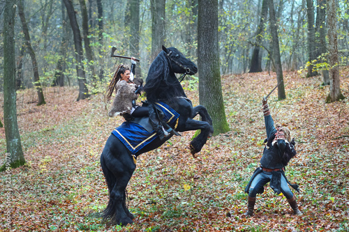 Portrait of dangerous scandinavian viking woman riding black horse in forest holding ax fighting with Viking warrior man in forest Canvas Print