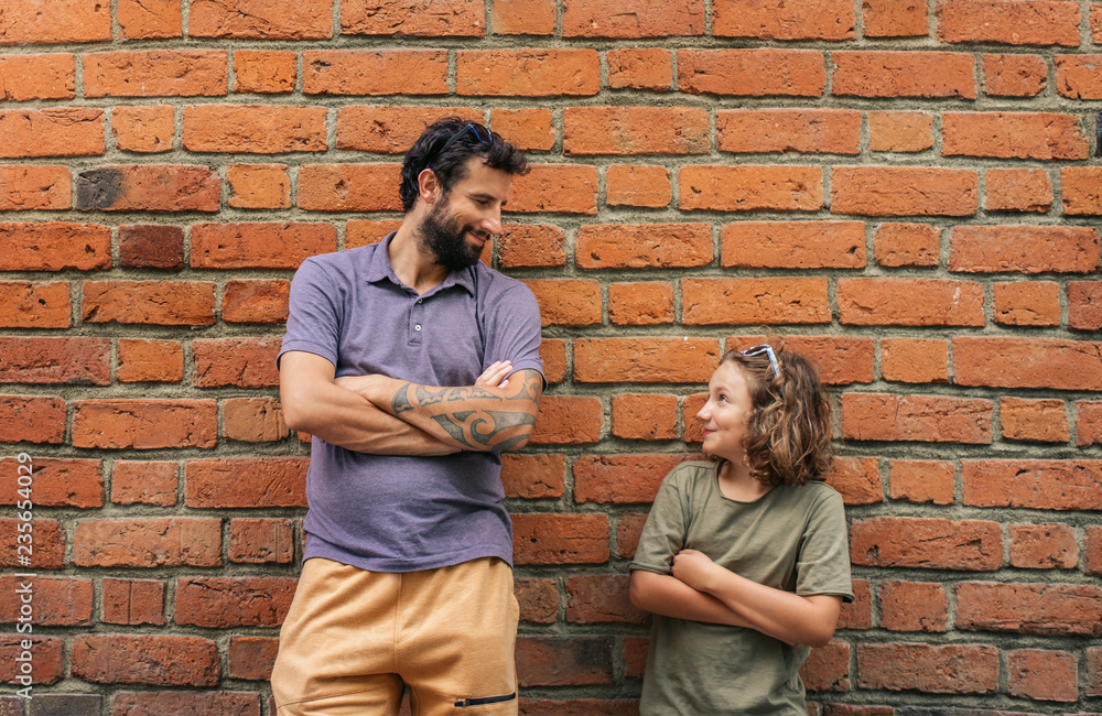 Fototapety, obrazy: Content son and father leaning against a brick wall outside
