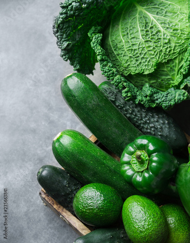 Fresh Organic Green Vegetables Savoy Cabbage Zucchini Cucumbers Bell Peppers Avocados on Black Stone Concrete Background. Rustic Style. Super foods Vegan Plant Based Diet Concept