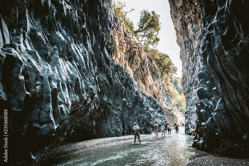 Photo TAORMINA, SICILY / ITALY - OCTOBER 2, 2018: Tourists walking in Alcantara Gorge and Alcantara river park in Sicily Island, Italy