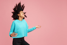 Portrait Of Excited African American Young Woman With Bright Smile Dressed In Casual Clothes Dance With Invisible Guitar Over Pink Background.
