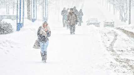 Young girl walk through snowfall resisting the pressure of a snowfall. Blizzard in an urban environment. Abstract blurry winter weather background