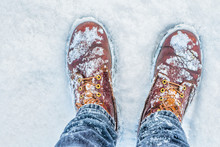 First Person View Of Legs In Brown Boots In The Snow. Snow On Boots While Walking In Winter