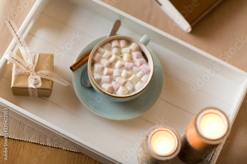 holidays and still life concept - hot chocolate with marshmallow, christmas gift and candles on table