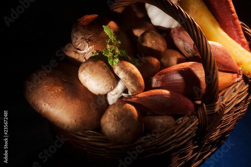Fotografía  Wicker basket full of mushrooms and root vegetables in low key lighting on a bla
