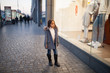 Child girl is standing next to shopwindow on city street in evening.