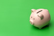 canvas print picture - Pink piggy Bank stands on the right on a green background. On the left there is a place in copyspace