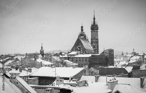plakat Krakow in Christmas time, aerial view on snowy roofs in central part of city. St. Mary's Basilica on Main Square. BW photo. Poland. Europe.