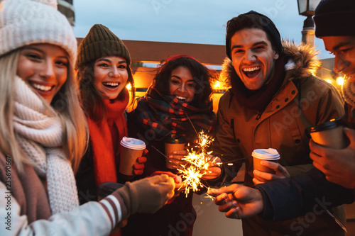 Fotografía  Young friends talking with each other drinking coffee outdoors winter concept holding bengal lights