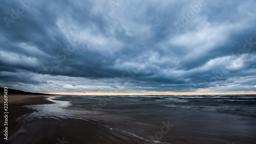 Stormy weather. A view of the wooden walkway on the Baltic seacoast on a cloudy autumn day, Latvia