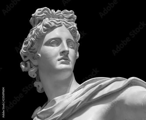 Stampa su Tela Portrait of a plaster statue of Apollo isolated on black