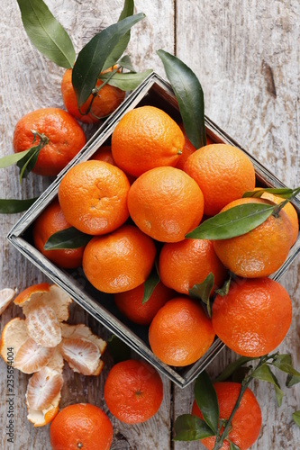 Tangerines with leaves in a wooden box.