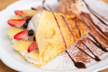 Side View Of Cold Crepe With Vanilla Ice Cream, Strawberry, Kiwi And Whipped Cream Topped With Chocolate Sauce On The Wooden Table. (Selective Focus With Shallow Depth Of Field)