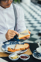 Cropped Asian Man Putting Butter On Toast Bread For His Breakfast.