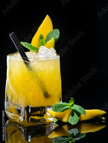 mango tiki alcoholic cocktail with mint on dark background
