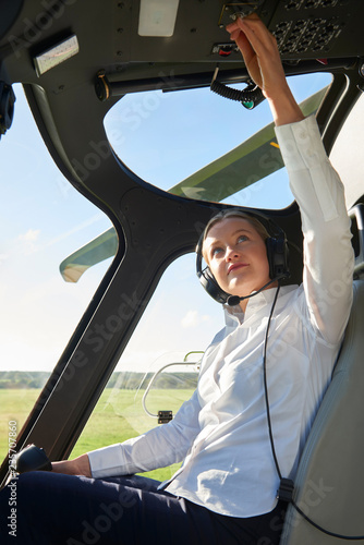 Female Pilot In Cockpit Of Helicopter Before Take Off