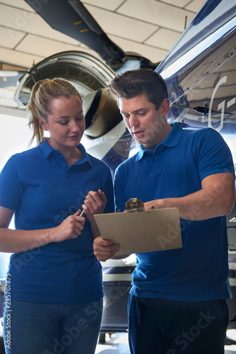 Aero Engineer And Apprentice Working On Helicopter In Hangar Looking At Clipboard