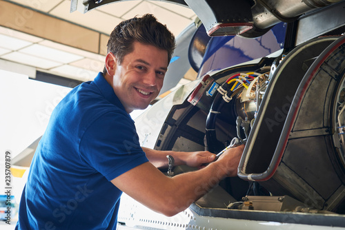 Portrait Of Male Aero Engineer Working On Helicopter In Hangar