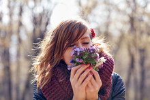 Cute Young Girl Smelling Nice Bouquet Of Flowers In Nature.
