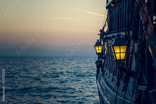 Photo sur Toile Navire old wooden vintage pirate ship on sea water surface in sunset evening romantic time with yellow light from soft focus lantern in overboard space
