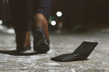 Lost Wallet Dropped From A Woman Pocket On The Night Footpath And Is Walking Away Silhouette Of Woman.