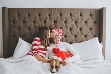 Happy Christmas Couple Snuggled In Bed With Puppy
