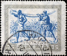 Two Black Men Carrying Elephant Tusk On Vintage Postage Stamp Of Liberia