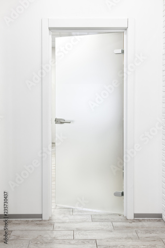 Minimalist white office interior with frosted glass door ajar