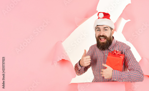 Bearded man with Christmas gift box shows thumb up through paper hole.