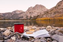 Book Near Cup On Rock Shore Near Lake