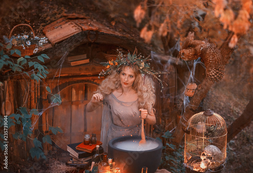 Attractive young girl with blond hair with an amazing lush wreath on her head in the forest is preparing a large cauldron Poster Mural XXL