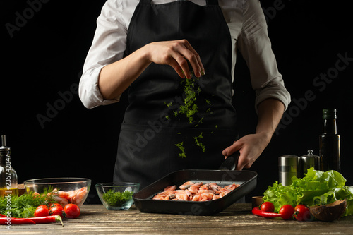 Obraz Professional chef sprinkles shrimps for salad, seafood and healthy food concept. Horizontal photo, menu, recipe book. - fototapety do salonu