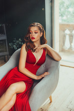Hot Young Adult And Imperious Woman, Dressed In A Long Scarlet Red Long Dress, Sexually Shows Her Nude Elegant Leg, Sitting On A Grey Chair In A Loft Room With Window To The Floor, Daring Style