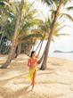 Woman wearing bikini by palm trees on beach