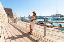Elegant Young Tourist Visitor Woman Looking At City Map On A Sightseeing Tour At Heraklion Venetian Port, Crete, Greece