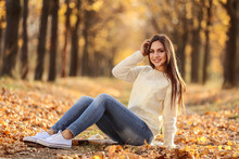 Beautiful Woman Sitting On Plaid In Autumn Park