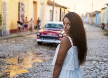 Beautiful Dark Skinned Young Lady In White Dress Standing In Front Of An Old Classic Car In The Old Streets Of Trinidad In Cuba.