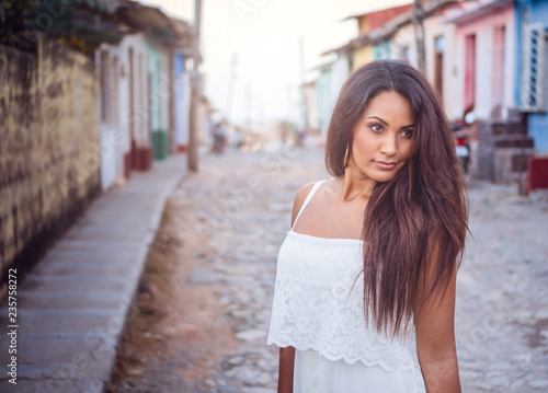 Photo  Beautiful dark skinned young lady in white dress standing in the old streets of Trinidad in Cuba