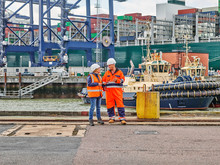 Dock Workers Standing Infront Of Tug And Cargo Container Ship On Digital Tablet